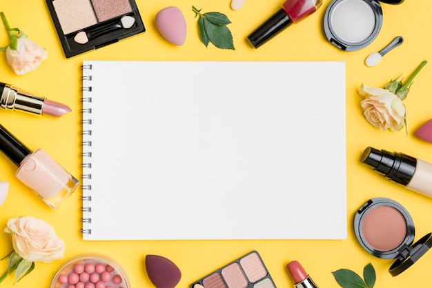 Top view different beauty products arrangement with empty notepad