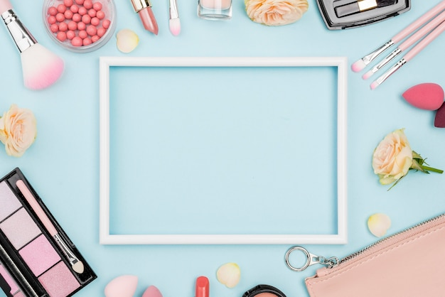 Top view different beauty products composition with empty frame