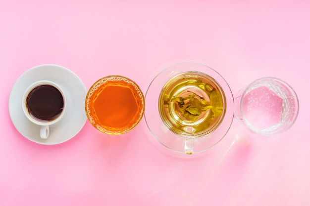 Top view of different beverages - drinking coffe, sparkling water, apple juice and green tea on pink  background. healthy life and diet concept