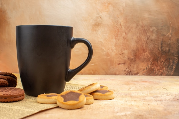 Top view of different biscuits and tea in a black cup on mixed color background
