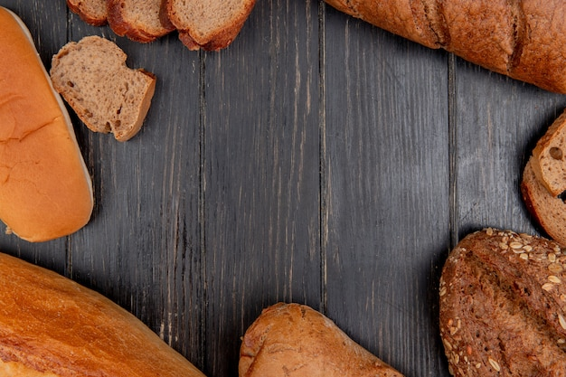 Top view of different breads as rye black baguette sandwich ones on wooden background with copy space