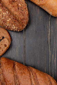 Top view of different breads as rye black baguette on wooden background