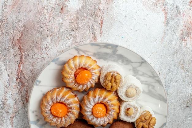 상위 뷰 다른 케이크 흰색 배경에 작은 과자 차 쿠키 비스킷 설탕 달콤한 케이크