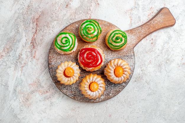 Вид сверху разные торты маленькие сладости на белом фоне печенье печенье сахар чай сладкий торт