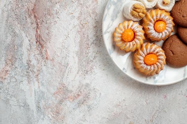 Vista dall'alto torte diverse piccoli dolci sullo sfondo bianco biscotto del tè biscotto zucchero dolce torta