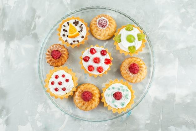 Vista dall'alto diverse torte con panna e frutta fresca sulla superficie chiara zucchero biscotto dolce