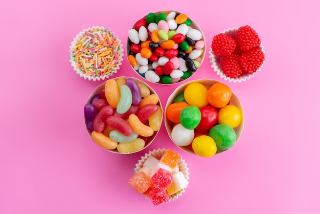 A top view different candies colorful inside little baskets on pink, sweet sugar color confiture
