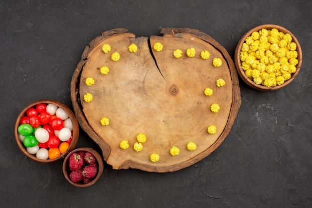 Vista dall'alto diverse caramelle caramelle colorate sullo zucchero arcobaleno color caramella scrivania scura