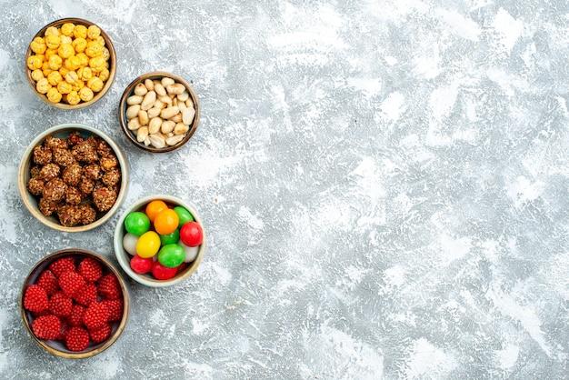 Вид сверху разные конфеты, орехи и конфитюры на белом пространстве
