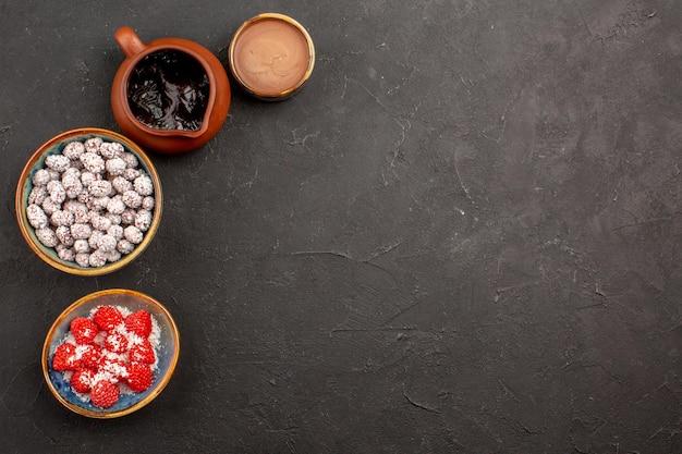 Вид сверху разные конфеты с шоколадным сиропом на темной поверхности цветного печенья с конфетами