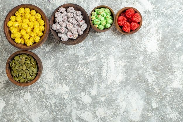 Top view different candies with confitures on white surface candy tea sugar cake many