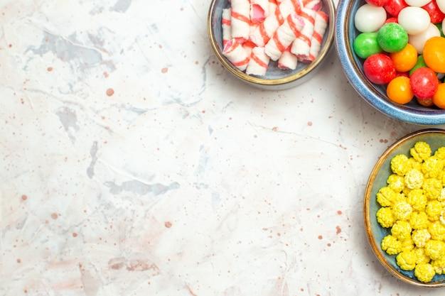 Vista dall'alto diverse caramelle con confetture su zucchero da tavola bianco caramelle arcobaleno