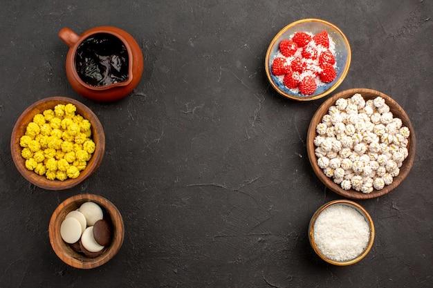 Vista dall'alto diverse caramelle con biscotti sul tè di caramelle color fiore di superficie scura