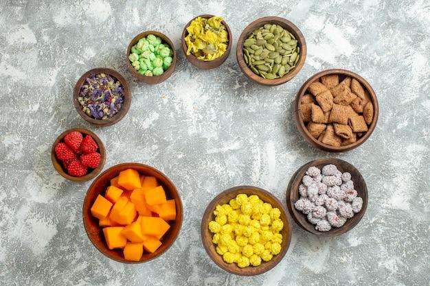 Вид сверху разные конфеты с цветами на белой поверхности цветных конфет, сахара, чая