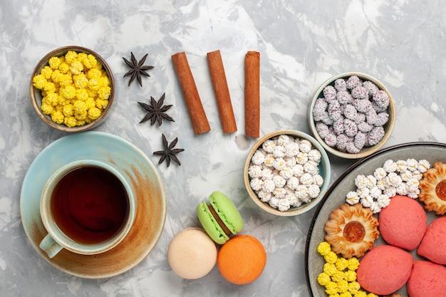 Vista dall'alto diverse caramelle con macarons francesi e tazza di tè sulla superficie bianca zucchero candito dolce cuocere i biscotti torta di tè torta