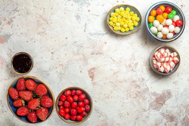 白いテーブルのキャンディーフルーツの色に新鮮なベリーとさまざまなキャンディーの上面図