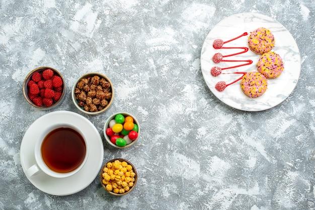 Вид сверху разные конфеты с орехами и чашкой чая на белом пространстве