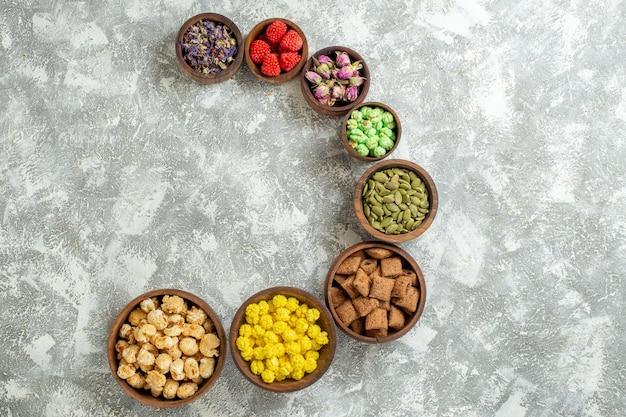 Vista dall'alto diverse caramelle con noci e fiori su superficie bianca caramelle tè zucchero torta molti