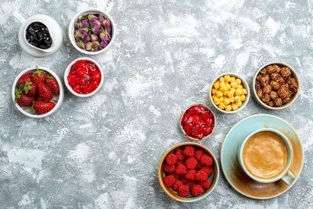 Top view different candies with nuts fruits and coffee on white space