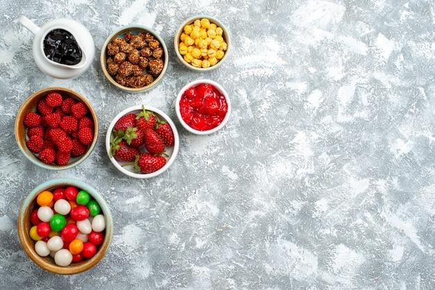 空白の上のナッツとさまざまなキャンディーの上面図