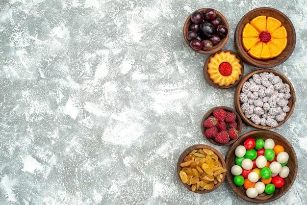 上面図白い背景の上のレーズンとフルーツとさまざまなキャンディーフルーツケーキキャンディーシュガー