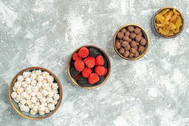 Вид сверху разные конфеты с изюмом на светлом белом фоне конфеты, сахар, чай, конфитюр
