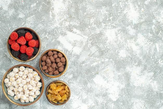 上面図白い背景のキャンディーシュガーティーコンフィチュールにレーズンとさまざまなキャンディー