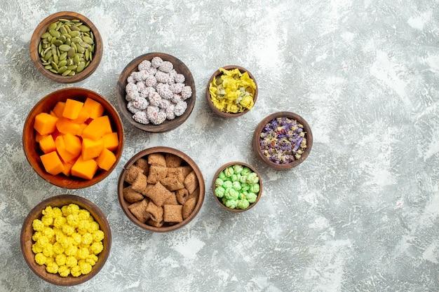 Вид сверху различных конфет с семенами и цветами на белой поверхности цветочного чая с конфетами