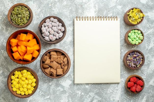 흰색 표면 꽃색 사탕 차에 씨앗과 호박이 있는 상위 뷰 다른 사탕