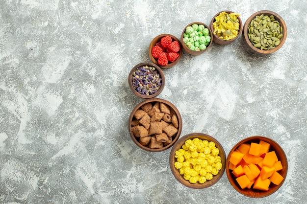 Vista dall'alto diverse caramelle con semi e fiori sul tè di caramelle color fiore di superficie bianca