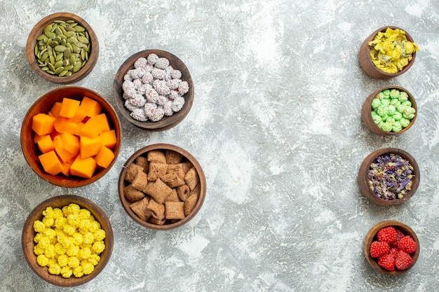 Vista dall'alto diverse caramelle con semi e zucca su tè di caramelle color fiore di superficie bianca