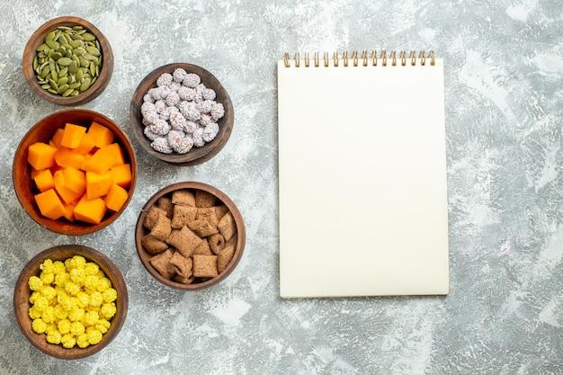 Vista dall'alto diverse caramelle con semi su tè di caramelle color fiore di superficie bianca