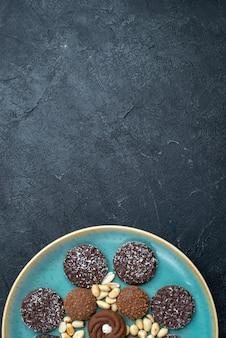 Вид сверху различных шоколадных печений с орехами на темно-сером фоне сахарного бисквита, сладкого пирога, пирога, печенья