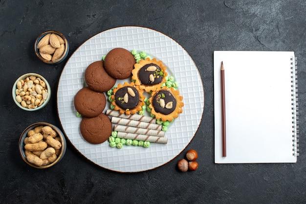 Вид сверху различных шоколадных печений с орехами на темно-серой поверхности сахарного бисквита, сладкого пирога, пирога