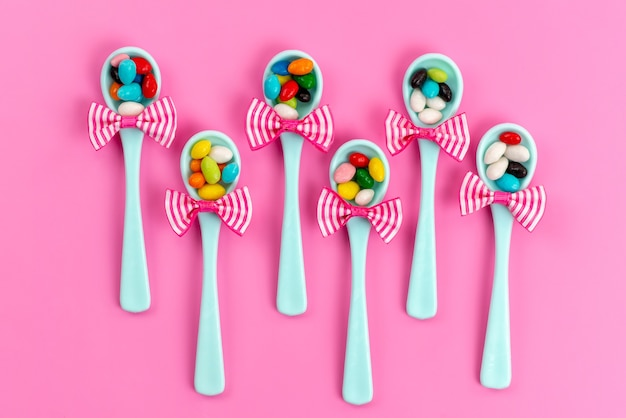Una vista dall'alto diverse caramelle colorate all'interno di cucchiai verdi con fiocco su zucchero arcobaleno rosa e dolce
