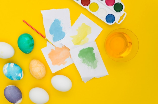 Top view of different colored eggs for easter and stained paper