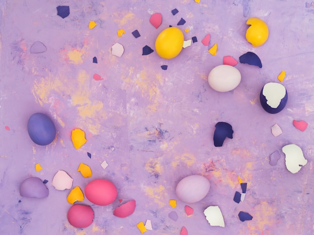 Top view of different colored eggs and scattered eggshell  on abstract background.