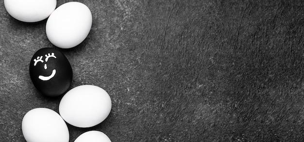Vista dall'alto di diverse uova colorate con facce per vite nere, movimento e copia spazio