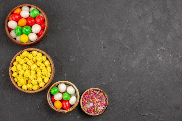 Top view different colorful candies on grey background color rainbow sweet tea