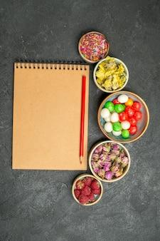 Vista dall'alto diverse caramelle colorate sulla scrivania grigia zucchero candito color arcobaleno