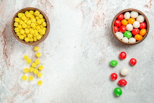Vista dall'alto diverse caramelle colorate su zucchero candito colore scrivania bianca