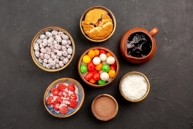Top view different colorful candies with confitures on dark surface color cookie candy tea biscuit