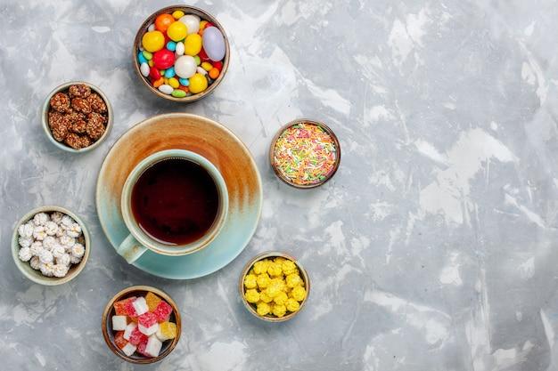 白い机の上にマーマレードとお茶のカップとさまざまなカラフルなキャンディーの上面図