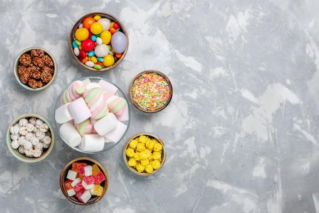 白い机の上にマーマレードとさまざまなカラフルなキャンディーの上面図