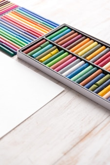 Top view of different colorful pastel paint and markers in boxes on white table