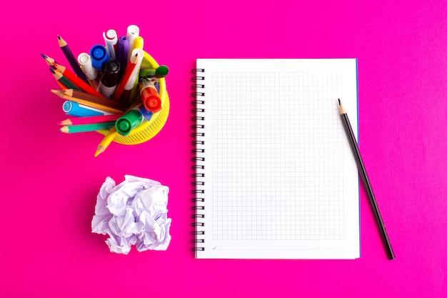 紫色の表面にフェルトペンとコピーブックが付いたさまざまなカラフルな鉛筆の上面図
