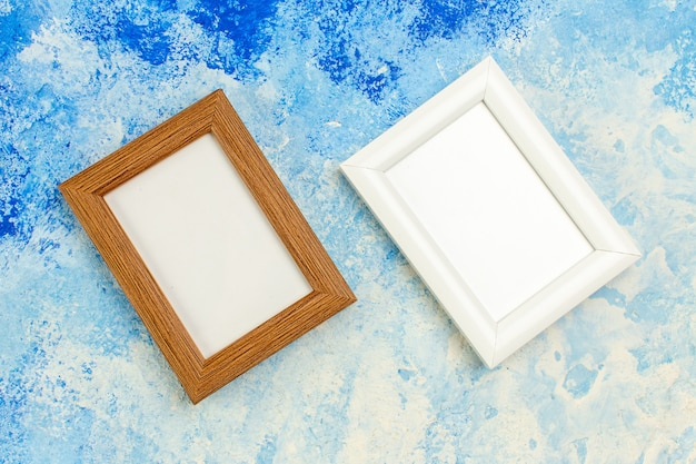 Top view different colors empty photo frames on blue white grunge