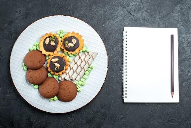 Vista dall'alto diversi biscotti al cioccolato a base di caramelle su sfondo grigio caramella bonbon zucchero dolce torta cookie