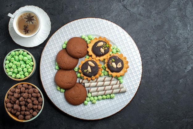 Top view different cookies chocolate based with different sugar candies on dark-grey surface candy bonbon sugar sweet cake cookie
