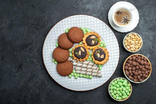 グレーのデスクキャンディーボンボンシュガースイートケーキクッキーにさまざまな砂糖菓子をベースにしたさまざまなクッキーチョコレートの上面図